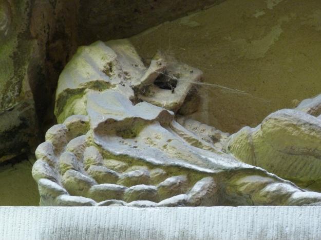 Detail of skeleton figure above gateway to churchyard