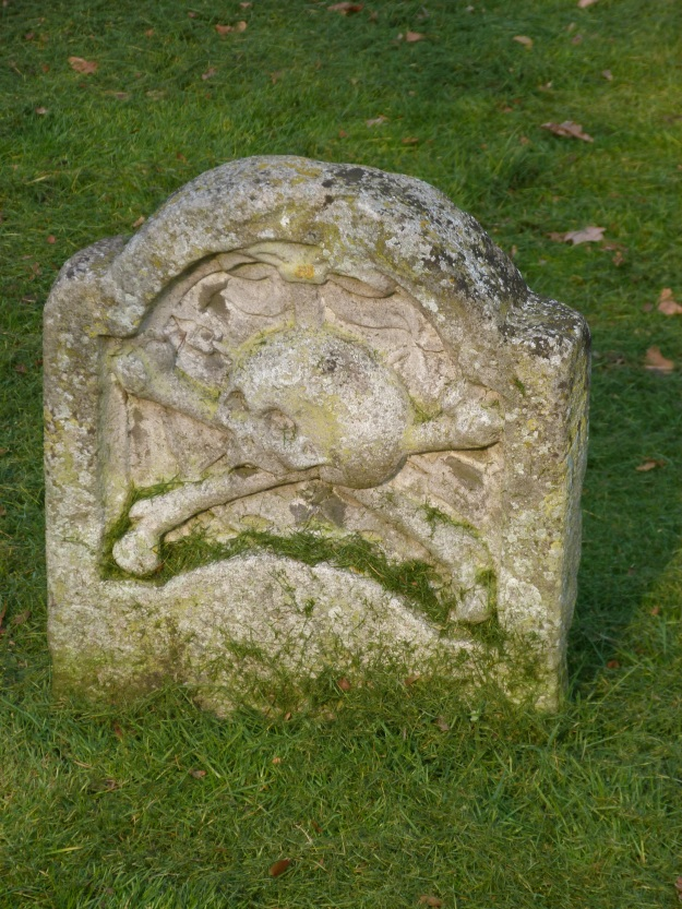 Old gravestone with skull and crossbones motif