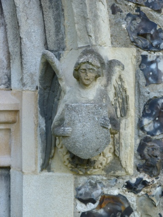 Carved stone angel beside doorway